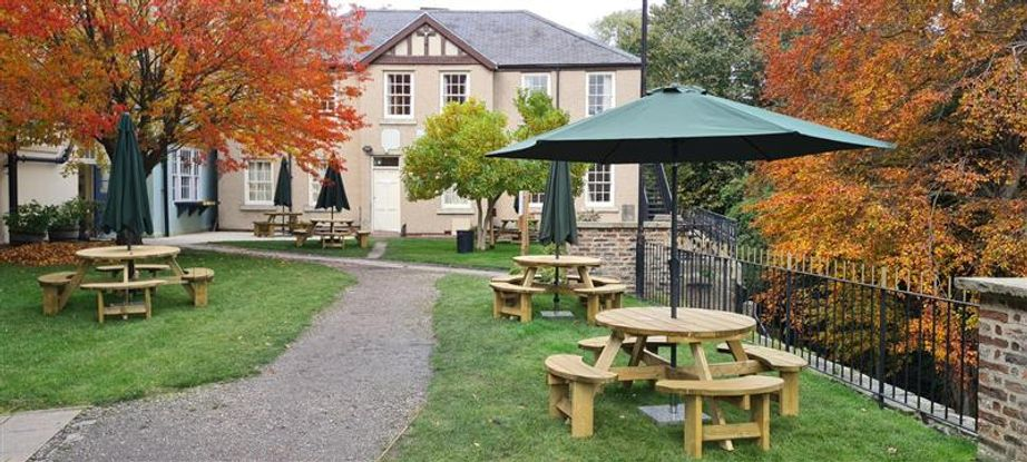 Beer garden with outdoor seating surrounded by autumnal trees