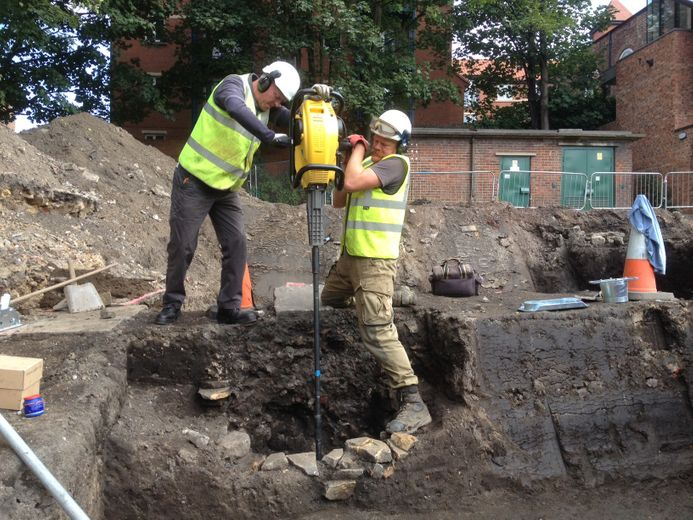 Two archaeologists using a handheld concussion borer to drill for palaeoenvironmental cores