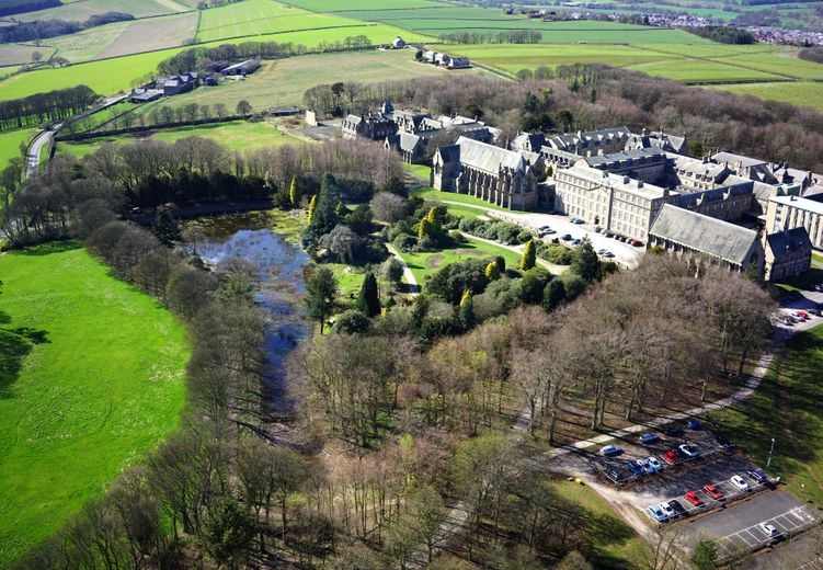 Overhead view from a drone showing historic building on the right and gardens and lake in the centre