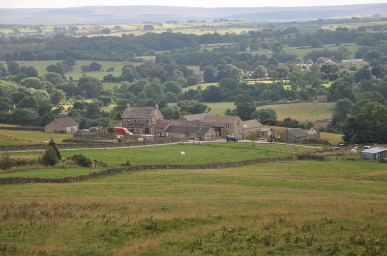 a photograph of typical northern English pastoral farmland with an old farm yard in the middle-distance and the Pennine Hills beyond