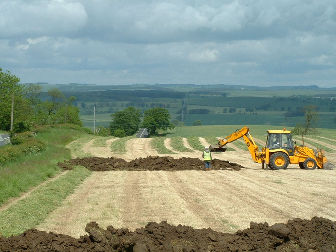 An archaeologist watching a yellow JCB excavate a trench in a field under a cloudy sky