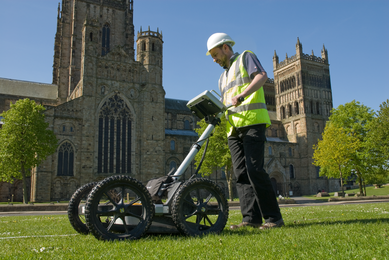 an archaeologist using GPR to survey Palace Green outside Durham Cathedral