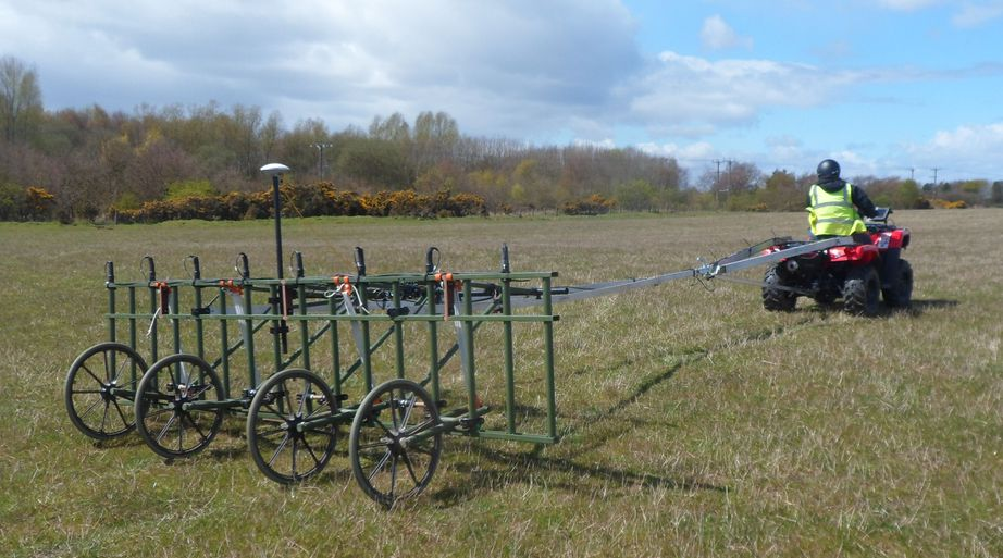 a quadbike pulling a cart-mounted geophysical survey system