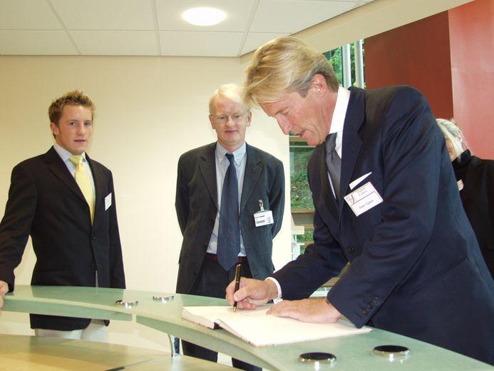 Sir Peter Ogden signs the register whilst opening the Ogden East building