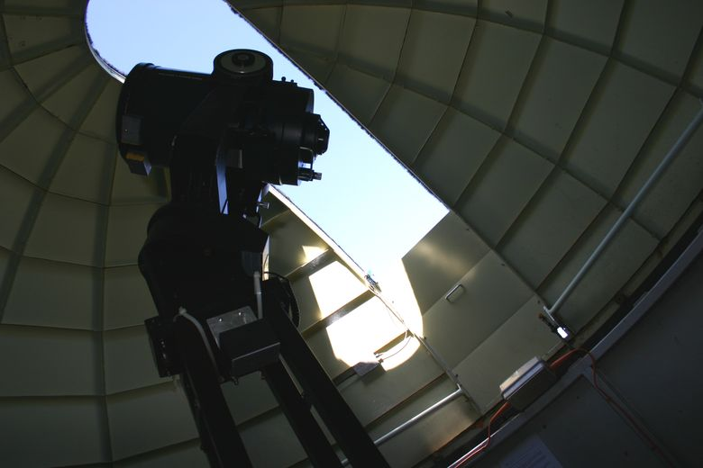 Image of telescope and light entering through opening in dome