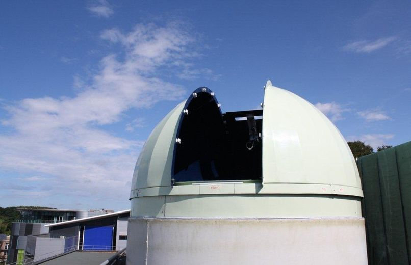 Open telescope dome with view of Calman Learning Centre and Science site