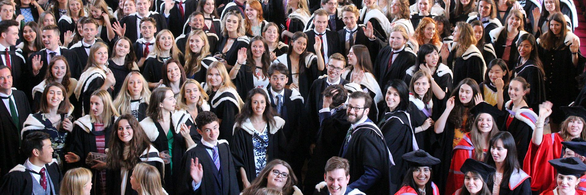 A large group of graduands in robes and hoods congregating in the Castle Great Hall