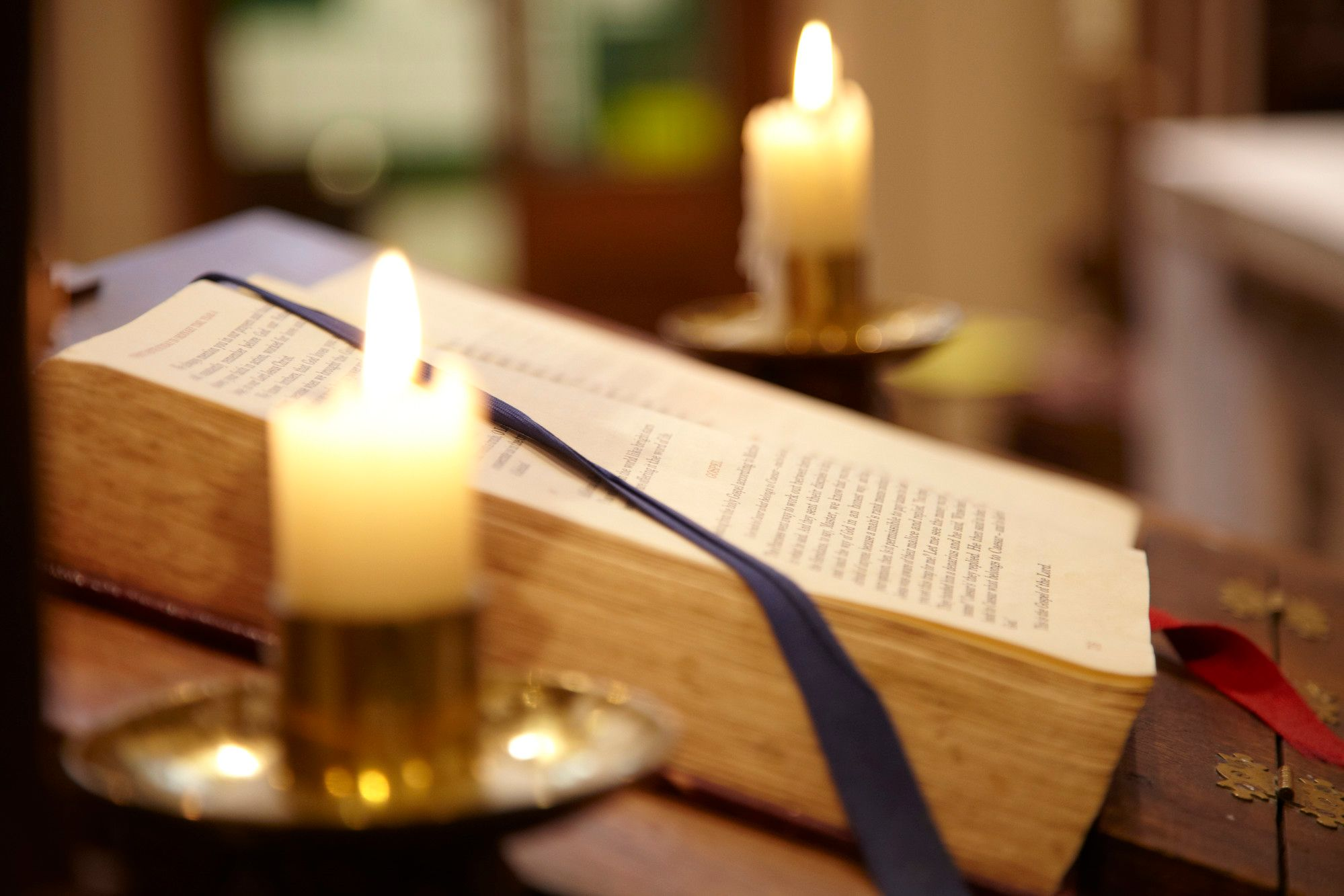 Close-up of church candle with book behind