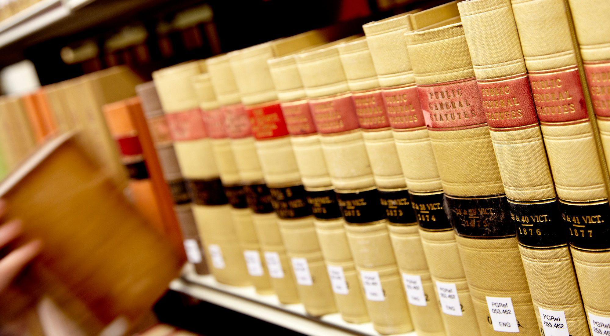 Close-up of hand pulling law book off shelf