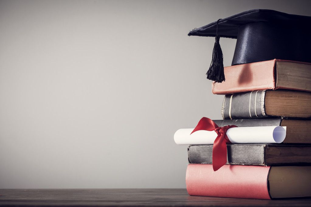 Graduation hat, certificate and books on a desk